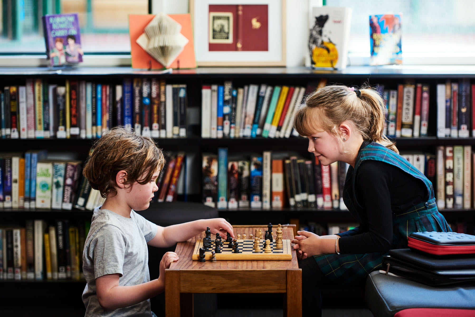 Two children playing chess in school library