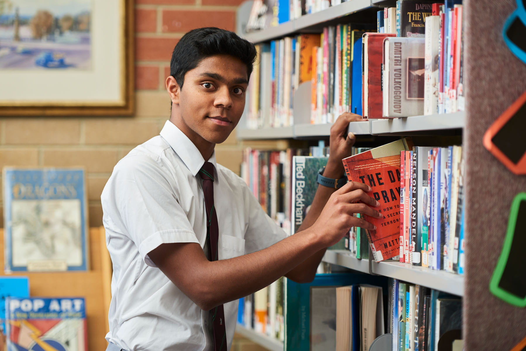 Teenager taking book off library shelf